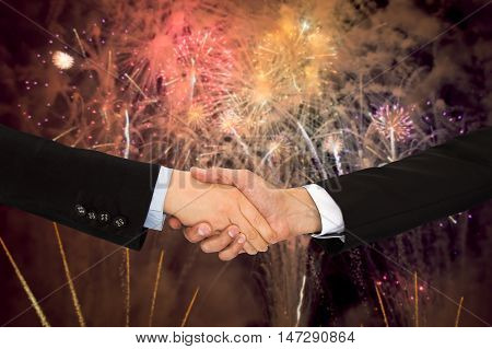 closeup of handshake between two business men with fireworks in the background like symbol of party planner