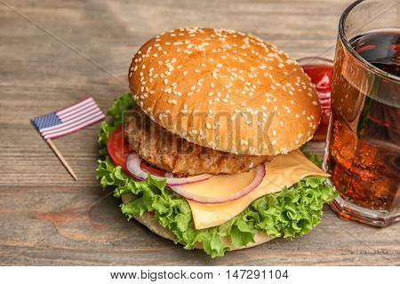 Tasty cheeseburger with coke on wooden table