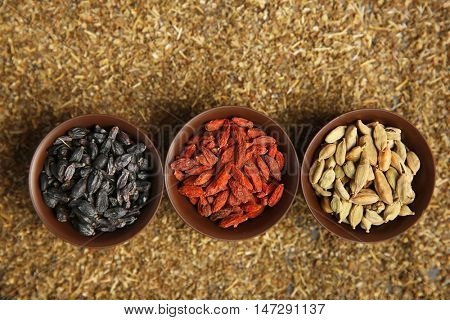 Cardamom, barberry and goji berries in bowls on spices background