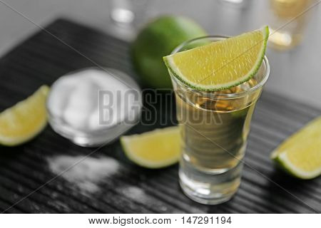 Shot of gold tequila with lime slices and salt on wooden board