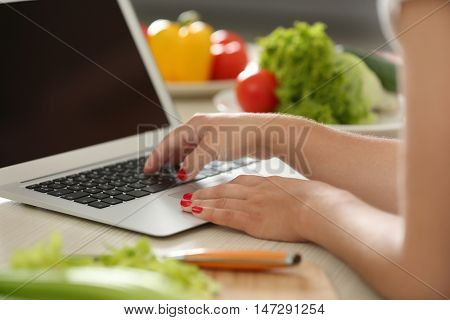 Girl with laptop on kitchen. Food blogger concept
