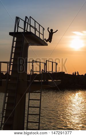 Courage and Jump: Silhouette of Child Jumping from High Board into Water Fun in the Summer