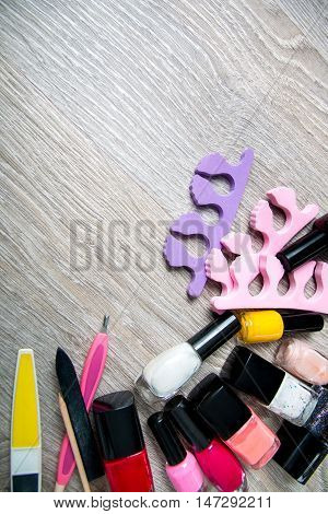 Set of nail polish and tools for manicure and pedicure  on a grey wooden background. Frame. Copy space. Top view.