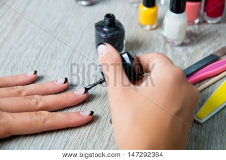 Black nail polish being applied to hand with tools for manicure on background. Beautiful manicure process. Close up.
