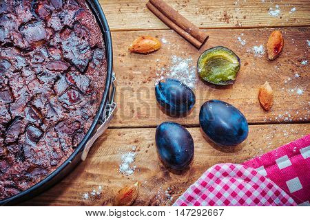 Chocolate clafoutis with plums in a baking pan, ripe fresh  plums and it`s stones, cinnamon, flour and cocoa powder on wooden background