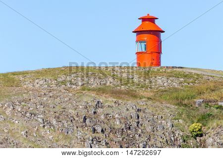 Cute little red lighthouse on a basalt island at the harbor of Stykkisholmur Iceland