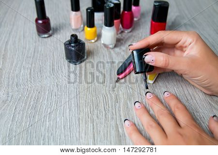 Black nail polish being applied to hand with tools for manicure on background. Beautiful manicure process.  Top view. Copy space. Frame.