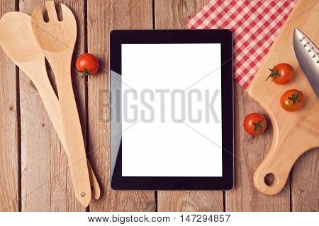 Digital tablet mock up template with cooking utensils and tomatoes. View from above