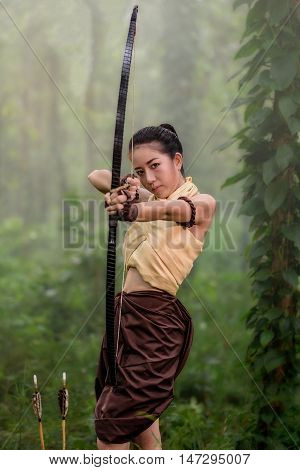 Beautiful ancient archery woman with bow and arrows aiming in forest background
