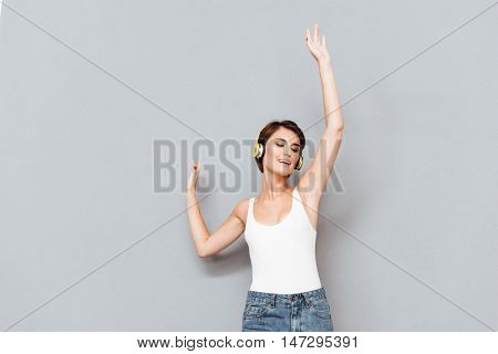 Portrait of a cheerful woman listening music in headphones and singing with raised hands up isolated on a gray background
