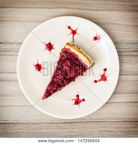 Piece of delicious cheesecake with strawberries on the plate. Sweet food. Cheese cake scene. One portion. Vibrant colors.