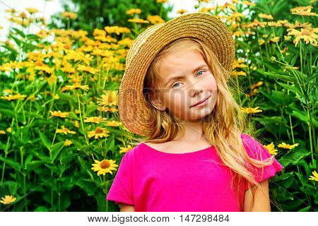 Portrait of a cute dreamy girl in a straw hat standing in a summer blooming park and smiling at camera. Happy childhood. Summer holidays.