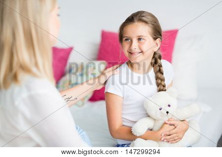 Happy girl with pigtail smiling at her mother