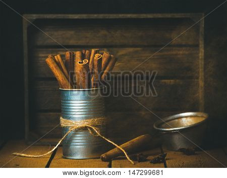 Cinnamon sticks in tin can and ground cinnamon in strainer, rustic wood bacground, selective focus, copy space