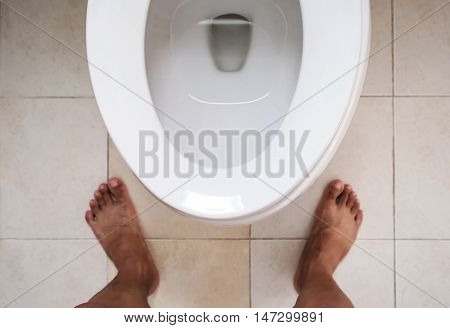 Top view, Toilet lavatory with bare feet standing, focus on lavatory