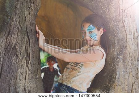 Small girl portrait with funny face art painting. Female child sit in tree with blue butterfly drawing on her face. Children event, birthday party and modern creative entertainment.