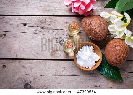 Coconuts and coconut oil on vintage wooden background. Selective focus. Flat lay. Natural organic spa products. Place for text.
