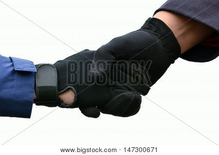Two Caucasian equestrian hands with black horse riding gloves shaking showing sportsmanship. Image isolated on white studio background.