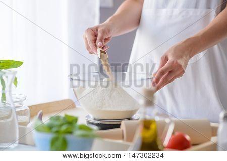 Woman Adding Powdered Yeast To Flour