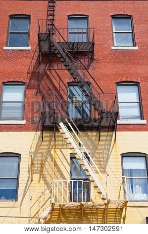The typical american fire escape ladder zigzagging across the face and windows.Portland USA