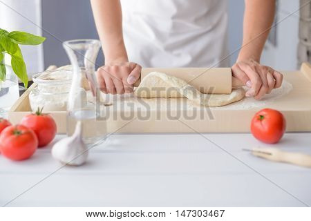 Woman Rolling Pizza Dough Using Rolling Pin.