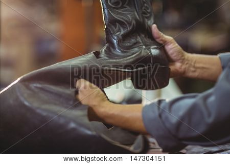 Cobbler making leather boots in workshop