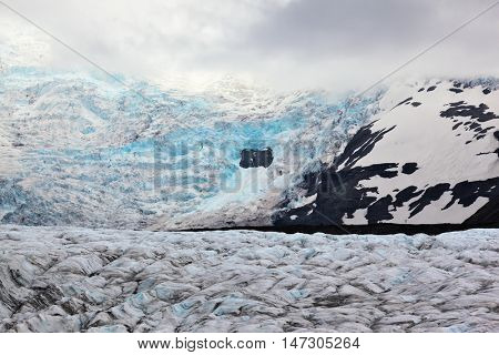 Blue ice covered ground black volcanic ash. The southern part of the huge Vatnajokull glacier. Skaftafell National Park