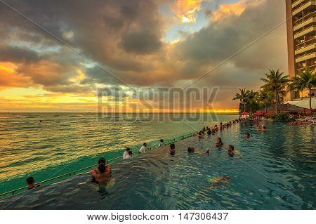 Waikiki Oahu Hawaii - August 20 2016: people of infinity edge swimming pool looking at the ocean twilight. Sheraton Waikiki Hotel in Waikiki Beach Honolulu. Summertime relaxing in luxury resort.