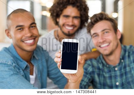 Young friends showing black screen of smartphone on camera. Three young men sitting in cafe using smartphone. Three guys holding a mobile phone with blank screen ready for your text or image.