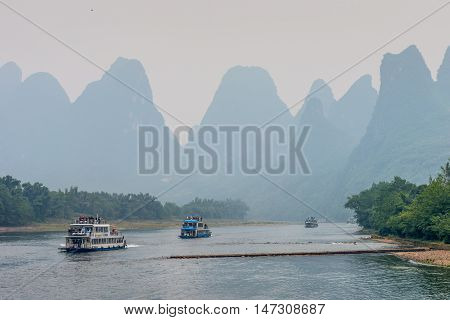 Yangshuo China - October 20 2013: A tourist boats packed with tourists travels the magnificent scenic route along the Li river from Guilin to Yangshuo in the haze.