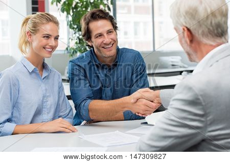 Handshake of a senior financial advisor with a young man and his girlfriend. Businessman handshake with couple during meeting signing agreement. Real estate agent shaking hands with happy couple.