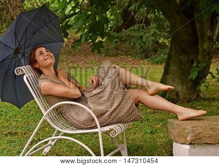 Outdoors young woman wearing retro style dress holding umbrella.