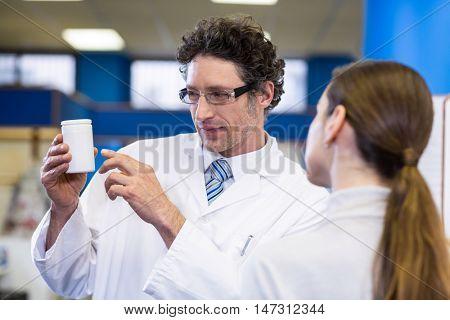 Pharmacist assisting the bottle of drug to customer in pharmacy