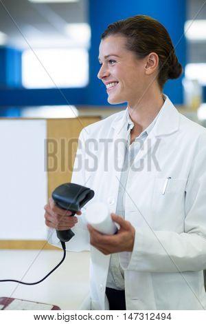 Smiling pharmacist using barcode scanner on medicine bottle in pharmacy