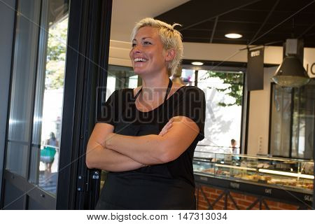 Confident small business bakery shop owner standing in her shop.