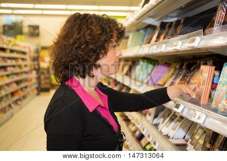 A Woman reading nutritional values at supermarket