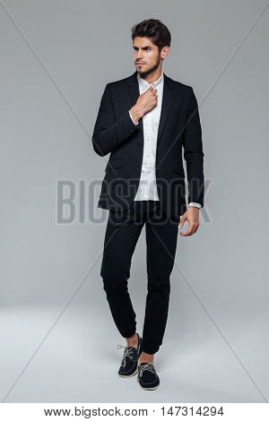 Full length of a handsome young man in black suit posing over grey background