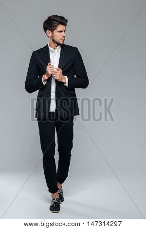 Full length of an attractive young man in black suit posing over grey background