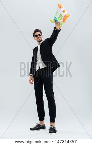 Smiling handsome man in sunglasses and black suit shooting with water gun over grey background
