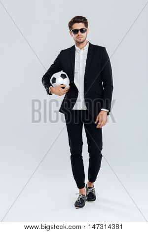 Full length portrait of a confident handsome man in sunglasses and black suit holding soccer ball over grey background
