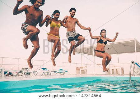 Enjoying pool party. Group of beautiful young people looking happy while jumping into the swimming pool together