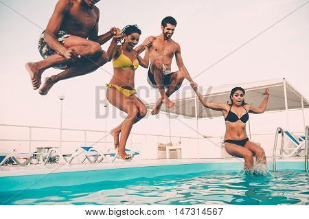 Enjoying pool party together. Group of beautiful young people looking happy while jumping into the swimming pool together