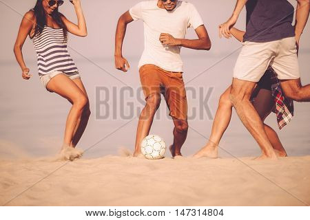 Beach ball with friends. Cropped image of young people playing with soccer ball on the beach