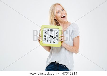 Happy cute young woman holding wall clock over white background