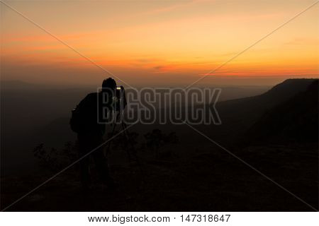 Silhouette of photographer when he is taking photograph on mountain at sunrise.