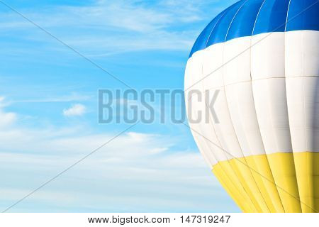 Multicolor blue, white, yellow air balloon in blue sky with cloud