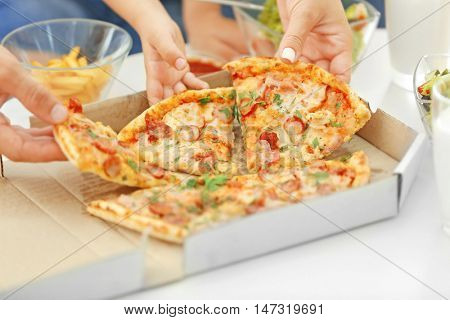 Hands taking pizza from table, closeup