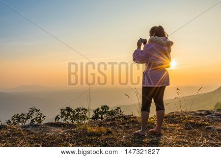 Young pink coat women is taking photograph by mobile phone on mountain at sunset.