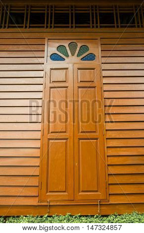 a typical wooden long window of Thai house with color stained glass on top