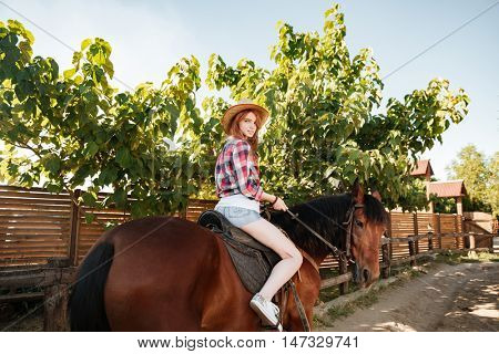 Portrait of beautiful redhead young woman cowgirl riding horse in village